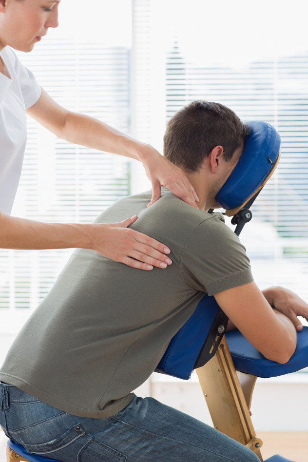 Therapist massaging man on massage chair in hospital